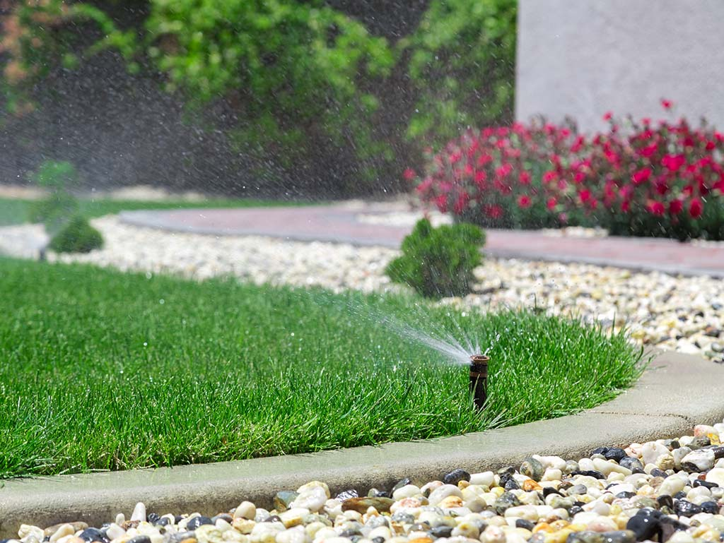 Garden irrigation system watering an irregularly shaped landscaped lawn.