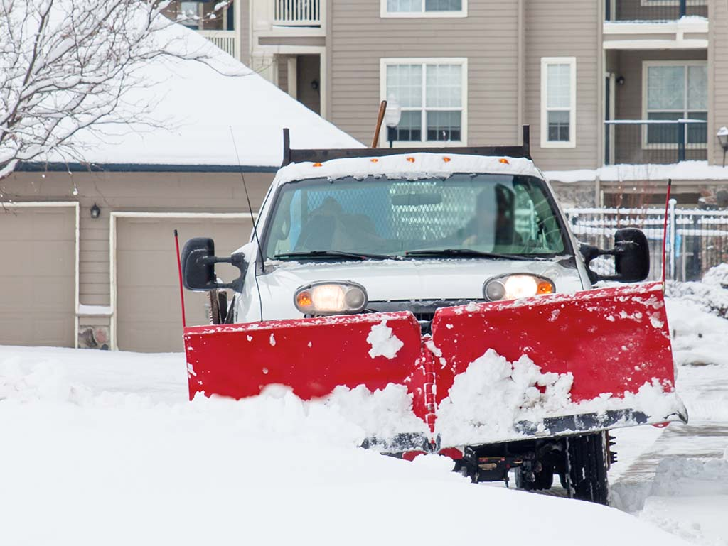 A large pickup truck with a snow plow clearing a driveway at an apartment complex.
